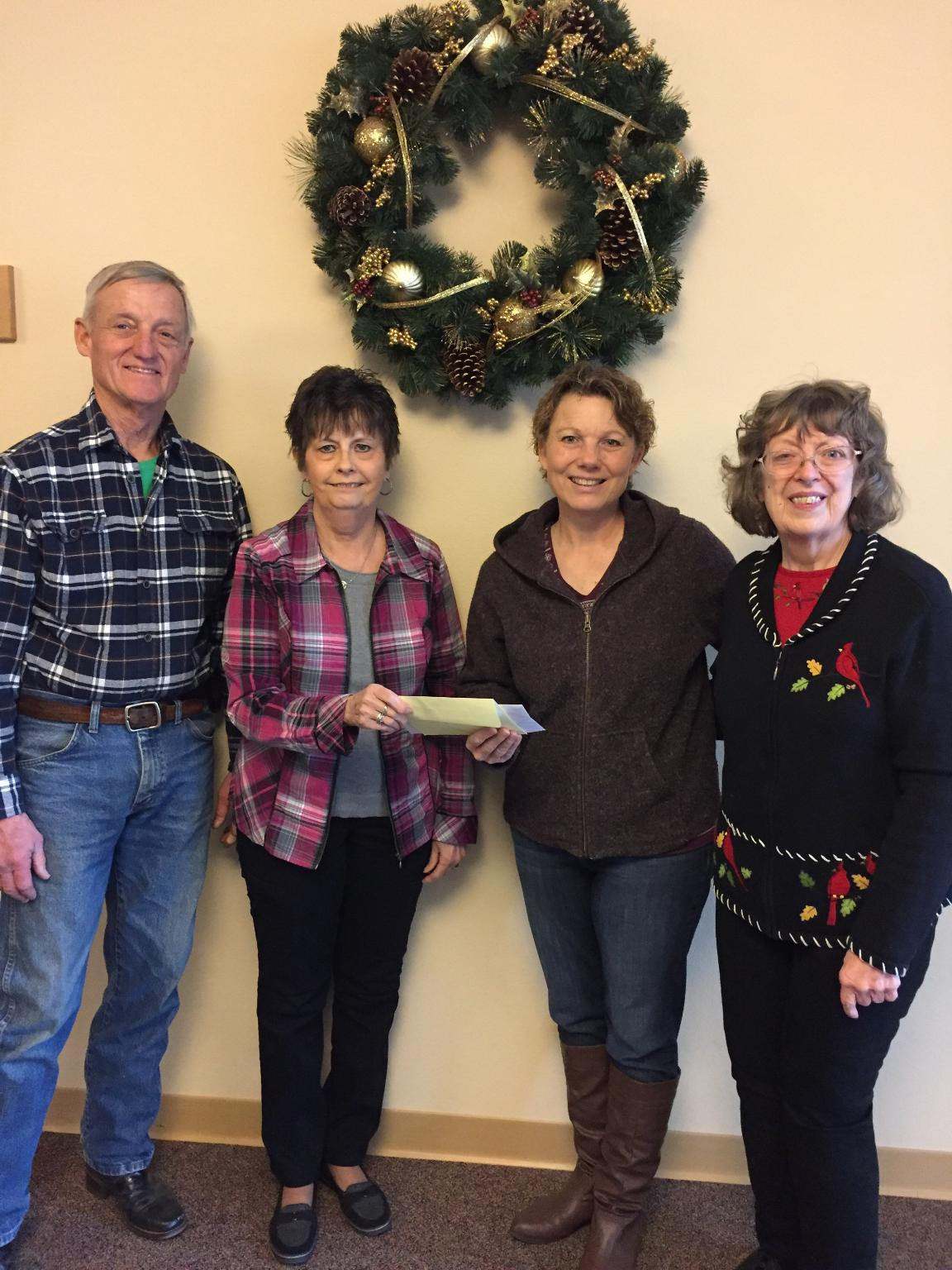 December 2, President Judy Spath and Anne Handschke present a check to Jeremiah's Crossing founders Roger and Kathleen Harris.